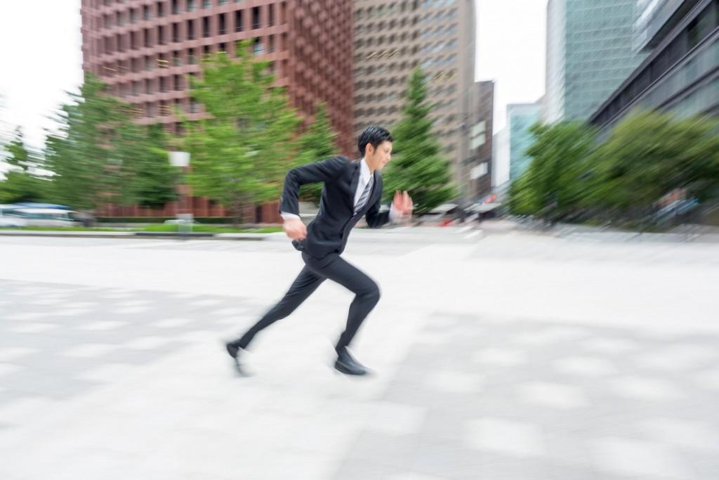 オフィス街を駆け抜けるスーツ姿の男性