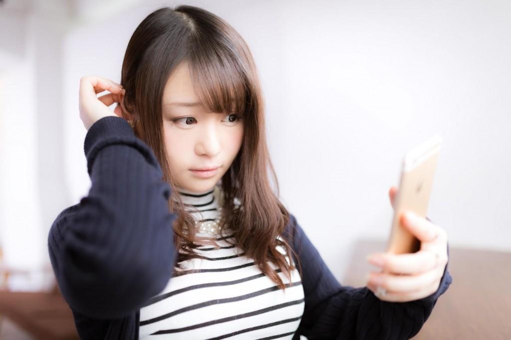 スマホを鏡代わりに髪の毛をさわる美女