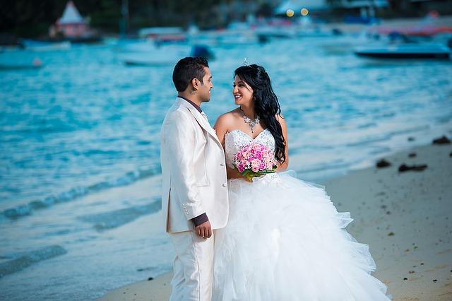 海辺で寄り添う白いタキシードの男性とウエディングドレスの美女