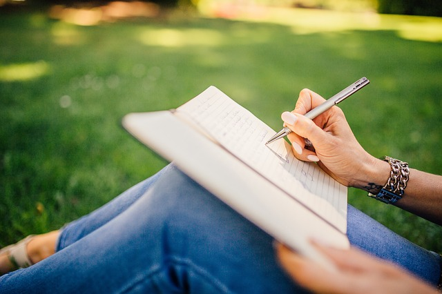 芝生に腰かけてノートに書き込みをする女性