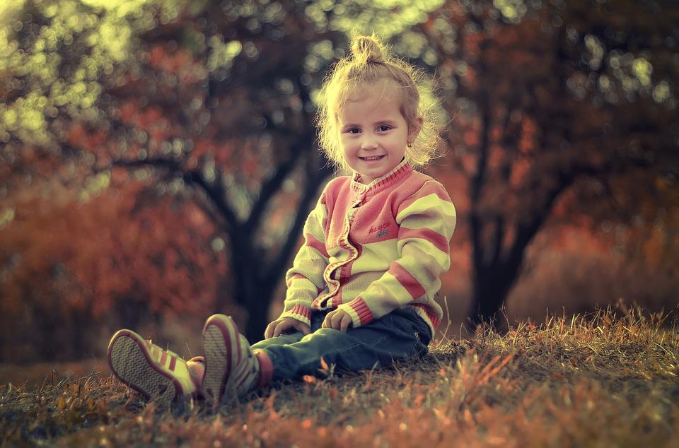 野原に座って微笑む少女