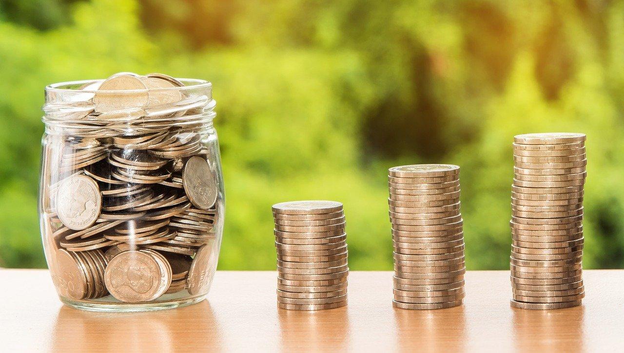 お金の詰まった瓶と積み上げられた硬貨