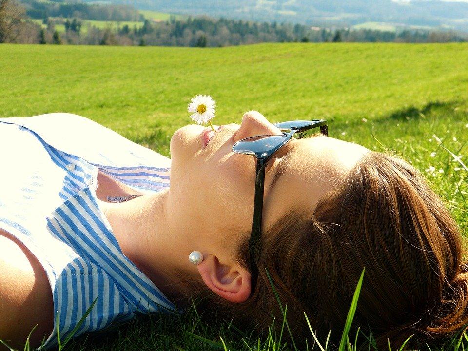 野原に寝転がる女性
