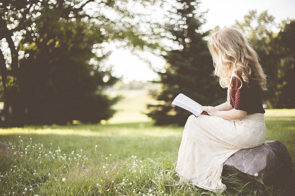 女の子が野原で本を読んでいる