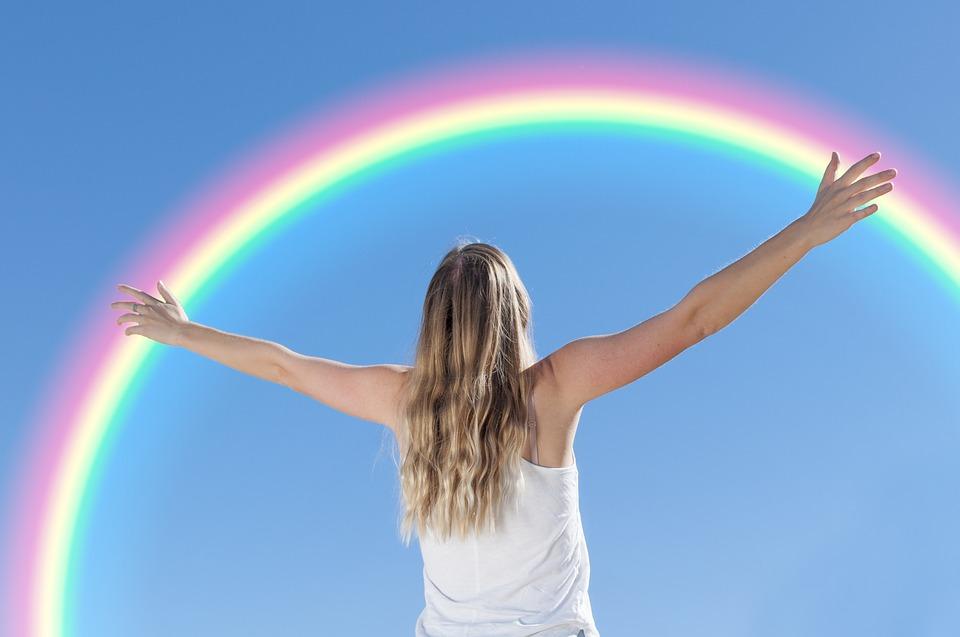 虹に手を伸ばす女性