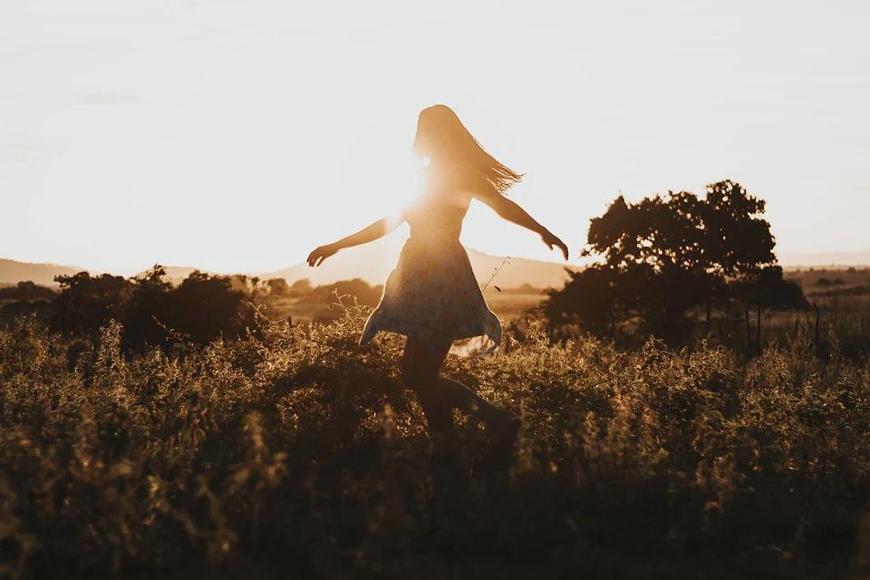 西日を受けて野原を歩く女性