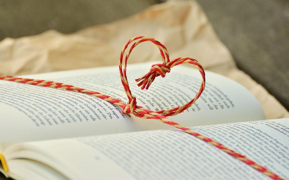 開いた本の上にハート形のひもが通っている