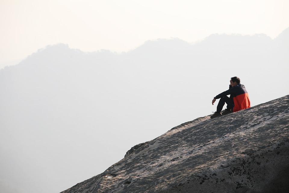 山の斜面で座り込む男性