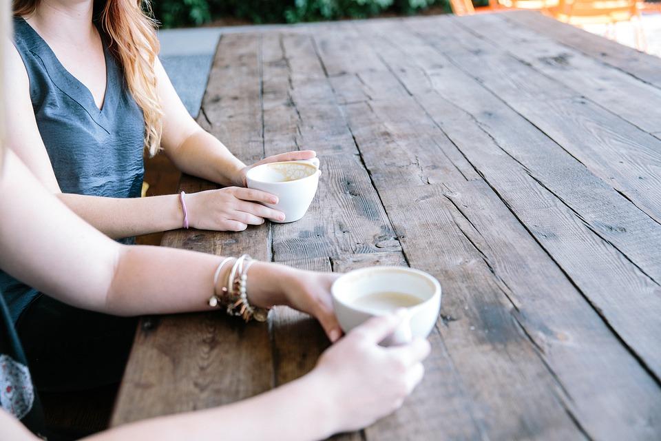 木のテーブルでお茶を飲みながら話をする女性二人