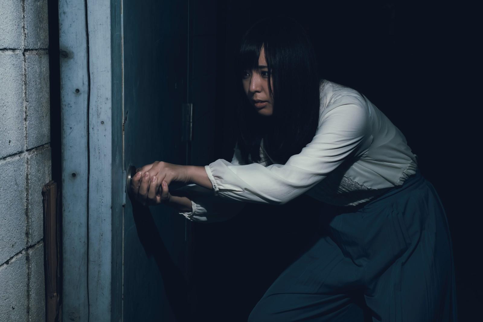 恐る恐るドアを開ける女性