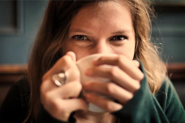 コーヒーカップを持ちながら微笑む女性