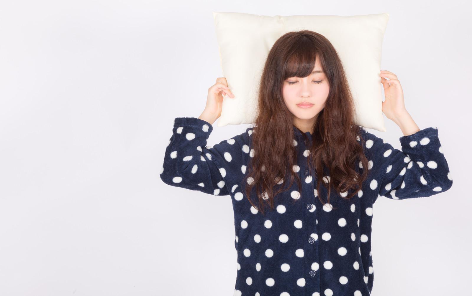 枕を持って眠る女性の画像