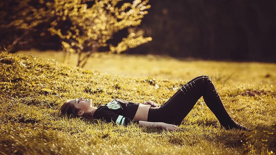 やる気がなく野原に寝転がっている女性