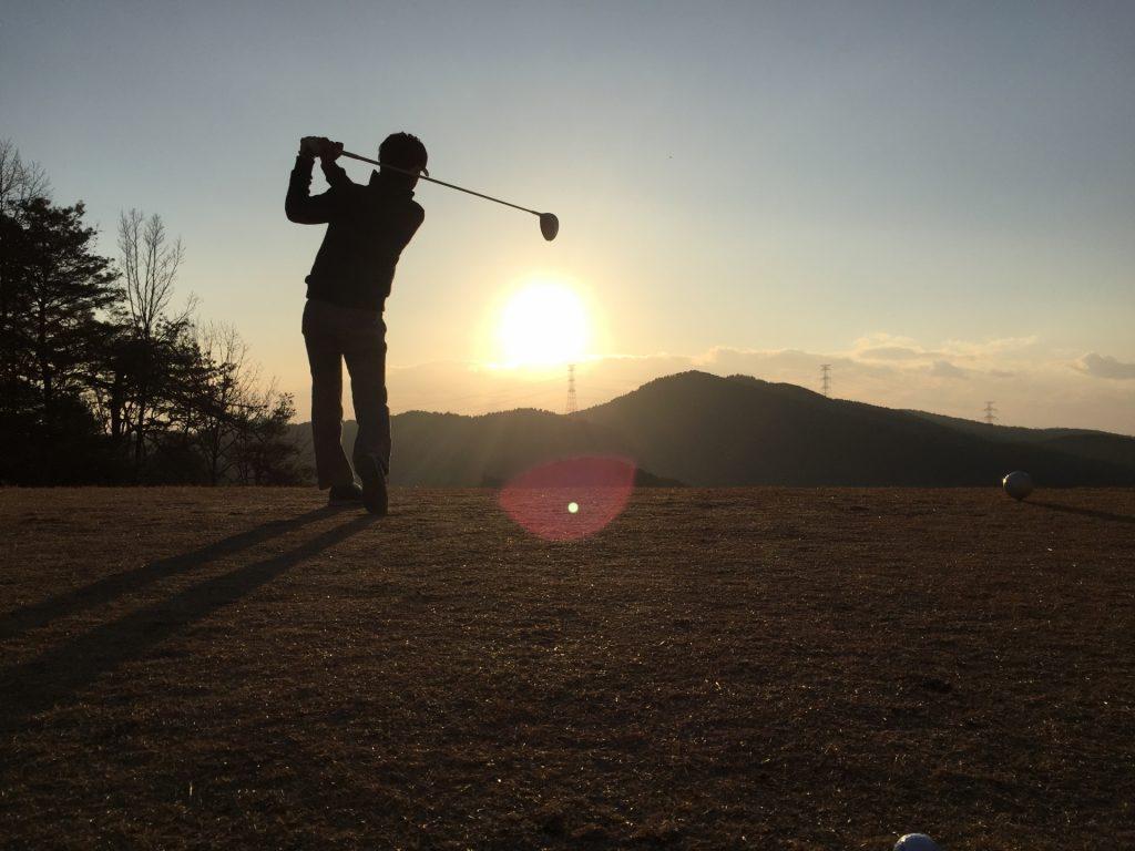 夕日とゴルフをする人