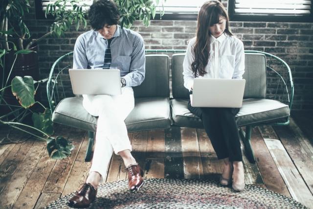 パソコンをしながら足を組む男女