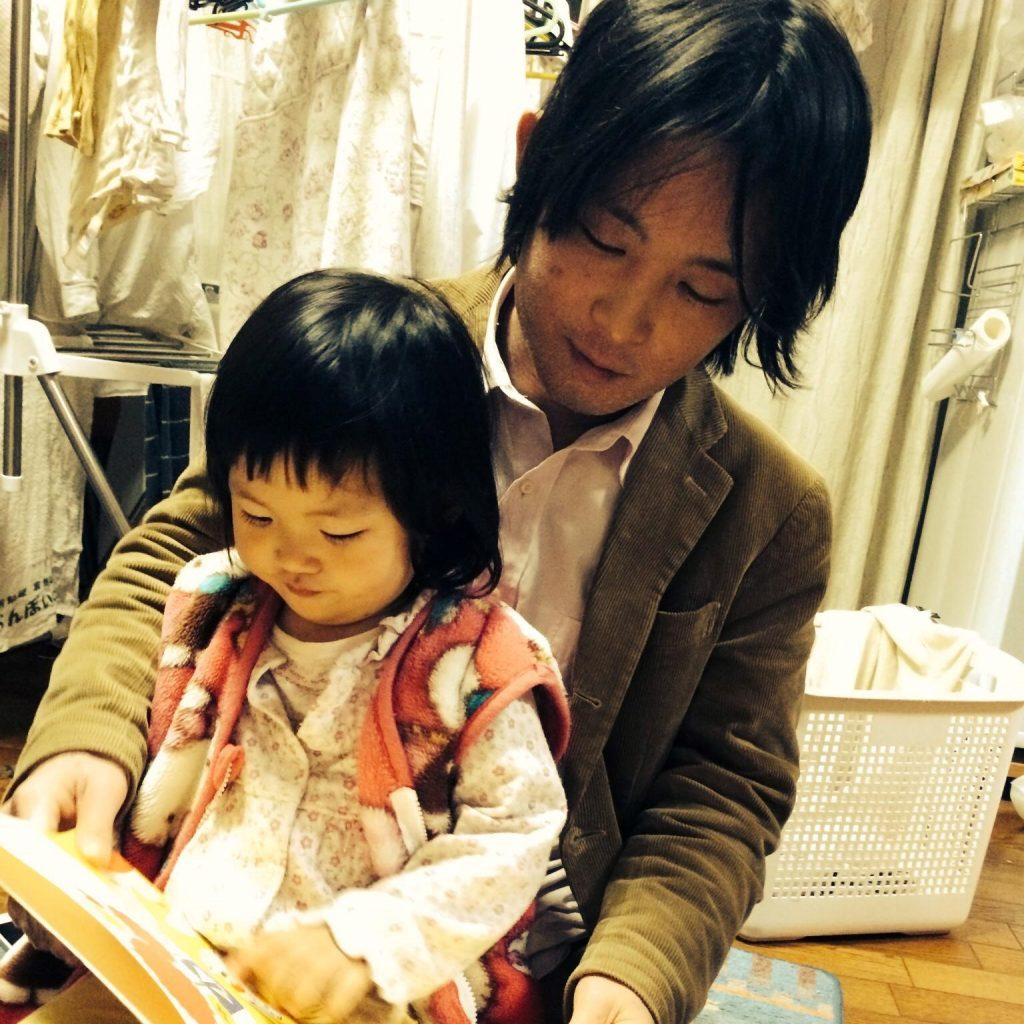 子どもに本を読んでいる写真