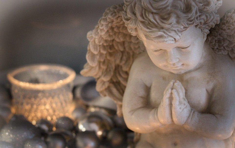 優しく手を合わせる天使の像