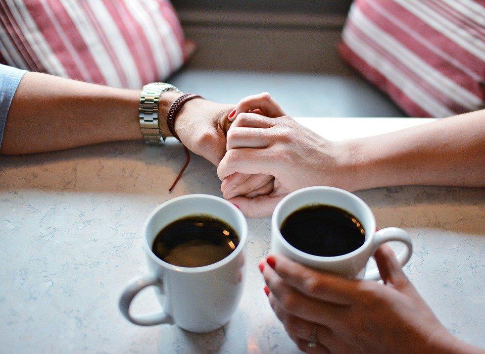 2人分のコーヒーと手を重ねる2人
