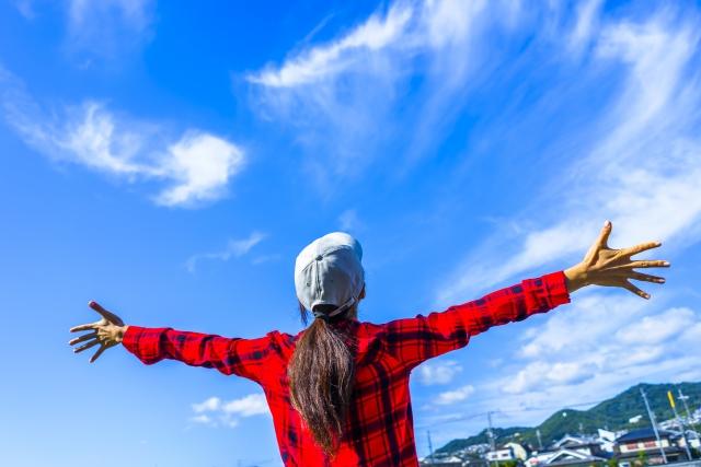 青空と手を広げる女性