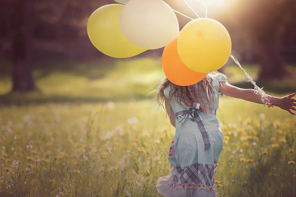 草原で黄色い風船を持っている女の子