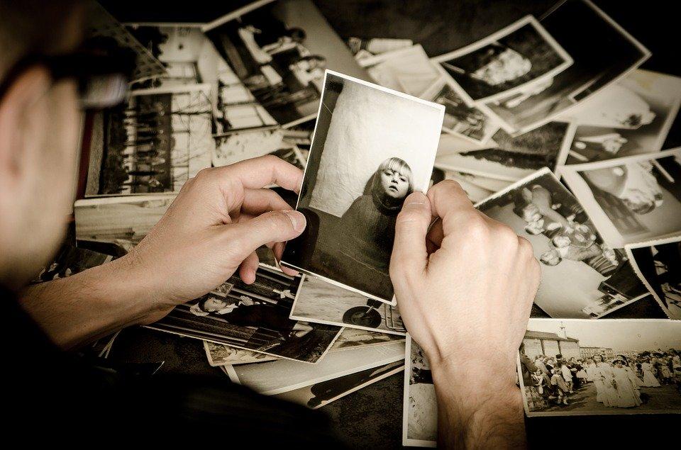 たくさんの古い写真を手に取っている