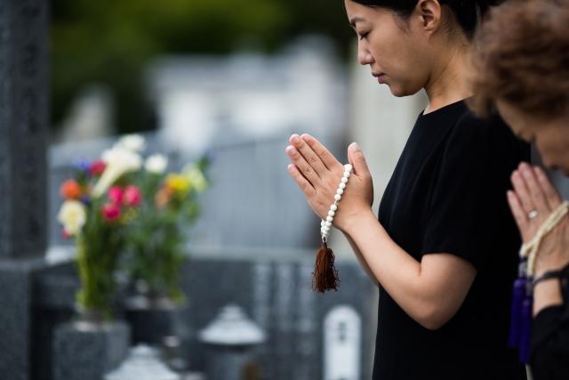 お墓の前で祈る女性