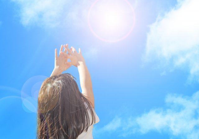空に手を伸ばす女性