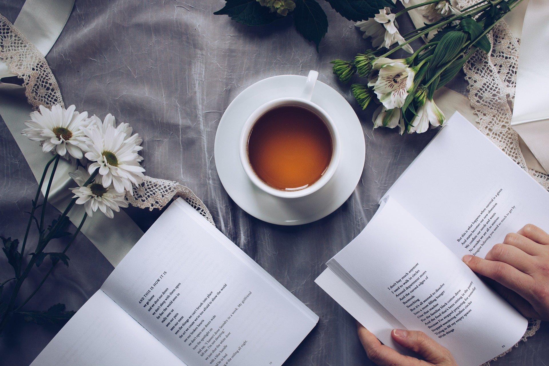 お茶をしながら本を広げる女性の手