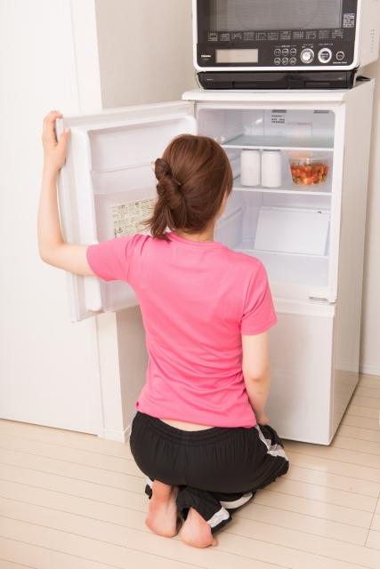 レンジが乗った冷蔵庫を覗く女性