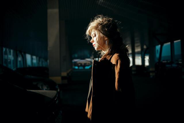 暗い場所でたたずむ女性