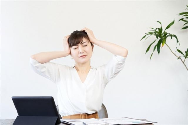 パソコンの前で悩む女性