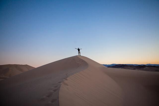 砂漠の小山に立つ人