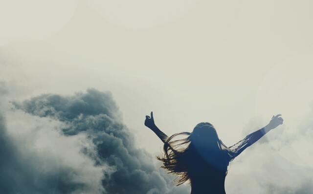 両手を広げて風を仰ぐ女性